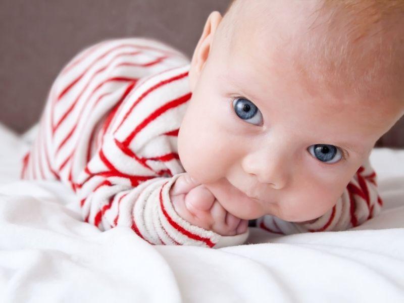 Bebê de bruços na cama