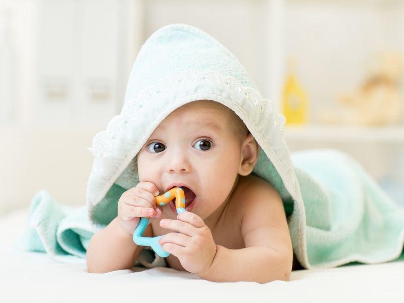 Bebê com brinquedo na boca